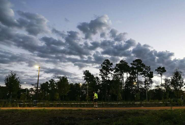The trail through Memorial Park's Eastern Glades lies between a new parking lot and bioswale and woodlands that will soon become a savanna.