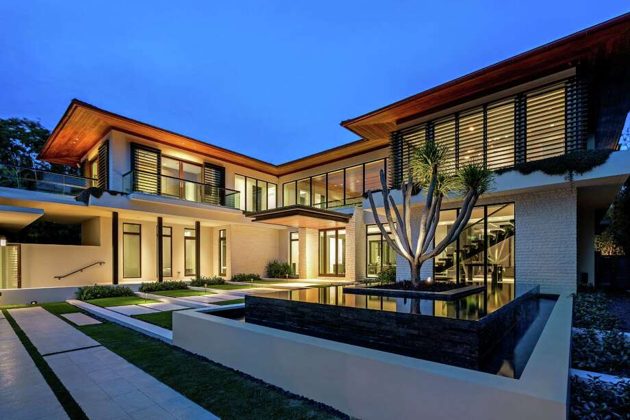 Hip-hop producer DJ Khaled paid $21.75 million for a modern Miami Beach mansion with five bedrooms and 12,750 square feet of living space. The two-story home, which blends organic materials with an overarching minimalist theme, features Cumaru wood ceilings, an elevator and a safe room. An 80-foot-long swimming pool sits across from the main house and adjacent to a two-story pavilion. Also on the grounds is a four-bedroom guesthouse. (Blue Ocean Photography) Photo: Blue Ocean Photography / Los Angeles Times