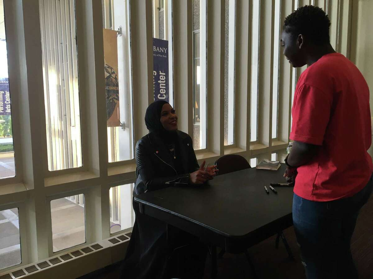 Olympic fencer bronze medalist Ibtihaj Muhammad meets with a fan for a memoir signing at the University at Albany Performing Arts Center on Wednesday Oct. 10, 2018.