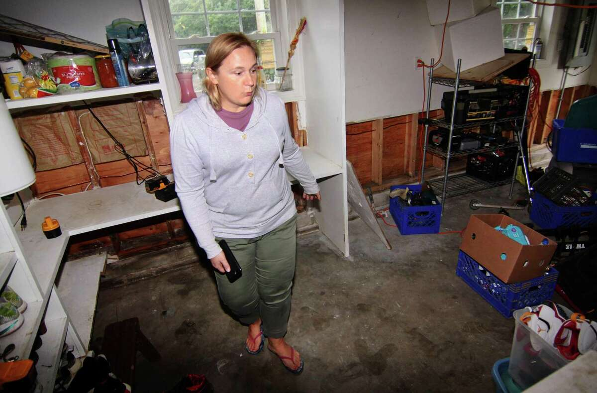 Renwick Drive resident Agnieszka Magtangob explains how much damage was done to her home from recent flooding in Bridgeport, Conn., on Thursday Oct. 11, 2018. Many homes in the neighborhood were damaged by the flooding of the Rooster River after a heavy rainstorm on Tuesday Oct. 2, 2018. Residents are angry that they have not been able to get any aid from FEMA because the mayor did not declare the area a disaster area.