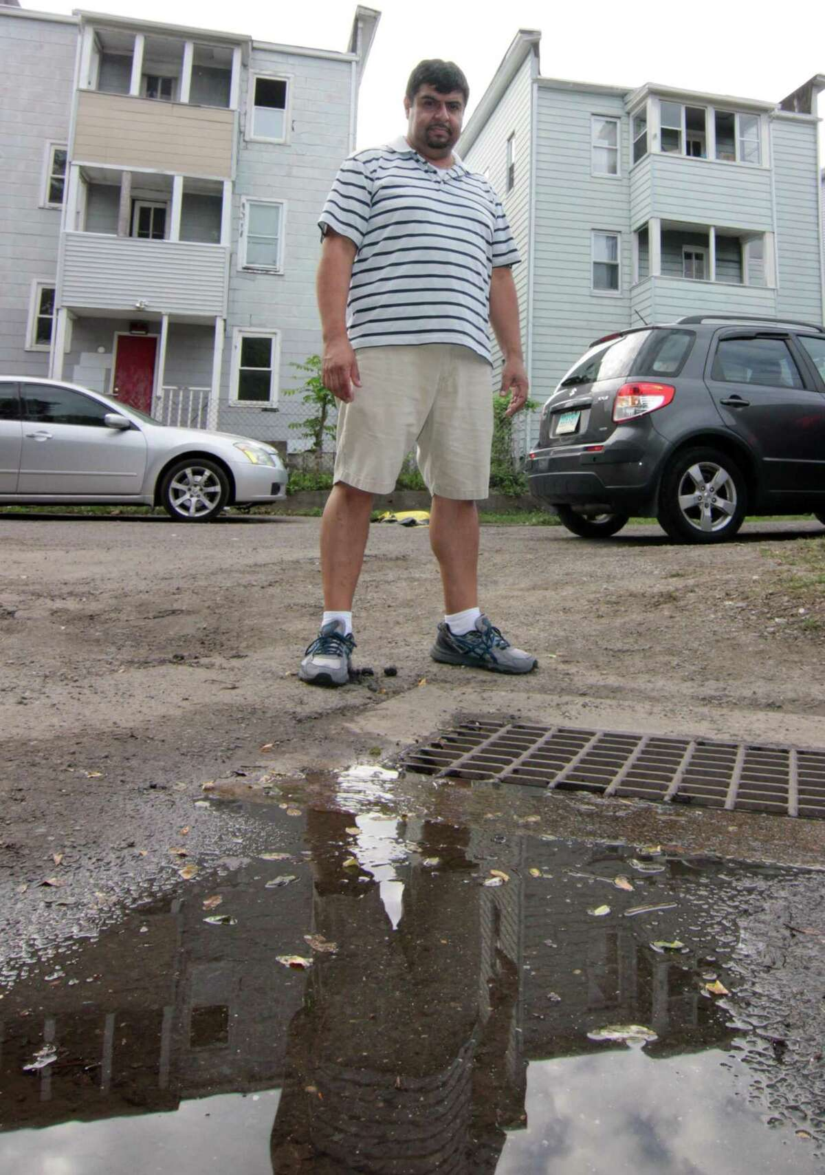 Wallace Court resident Pedro Quiroga stands near a drain that constantly backs up and floods the whole street in Bridgeport, Conn., on Tuesday Oct. 9, 2018. Many homes in the neighborhood were damaged by the flooding, including Quiroga's, after a heavy rainstorm on Tuesday Oct. 2, 2018.