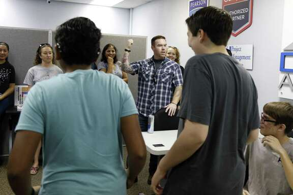 Shaun Herron, co-founder and president of GhostWire Academy, gives students a lesson Sunday before they take a CompTIA IT exam for certification at Dynamic Advancement, a professional development firm at Port San Antonio.