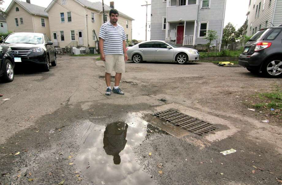 Wallace Court resident Pedro Quiroga stands near a drain that constantly backs up and floods the whole street in Bridgeport, Conn., on Tuesday Oct. 9, 2018. Many homes in the neighborhood were damaged by the flooding, including Quiroga's, after a heavy rainstorm on Tuesday Oct. 2, 2018. Photo: Christian Abraham / Hearst Connecticut Media / Connecticut Post