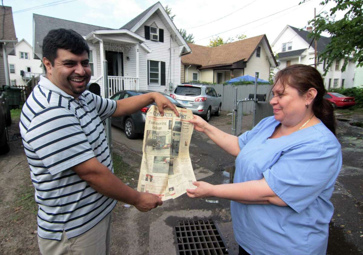 Wallace Court resident Pedro Quiroga and his wife Jacqueline hold up an edition of the Connecticut Post where they were rescued in 2007 due to flooding where water constantly backs up in Bridgeport, Conn., on Tuesday Oct. 9, 2018. Many homes in the neighborhood were damaged by the flooding, including Quiroga's, after a heavy rainstorm on Tuesday Oct. 2, 2018.