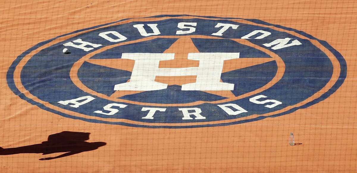 Players and staff walk by the Houston Astros logo on the field during workouts at Minute Maid Park, Thursday, October 11, 2018, in Houston, as the Astros prepare to leave for Boston for the ALCS.