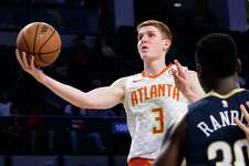 Atlanta Hawks rookie guard Kevin Huerter (3) goes to the basket past the defense of New Orleans Pelicans forward Julius Randle during the second half of a preseason basketball game Monday, Oct. 1, 2018, in Atlanta. The Hawks won 116-102. (AP Photo/John Amis)