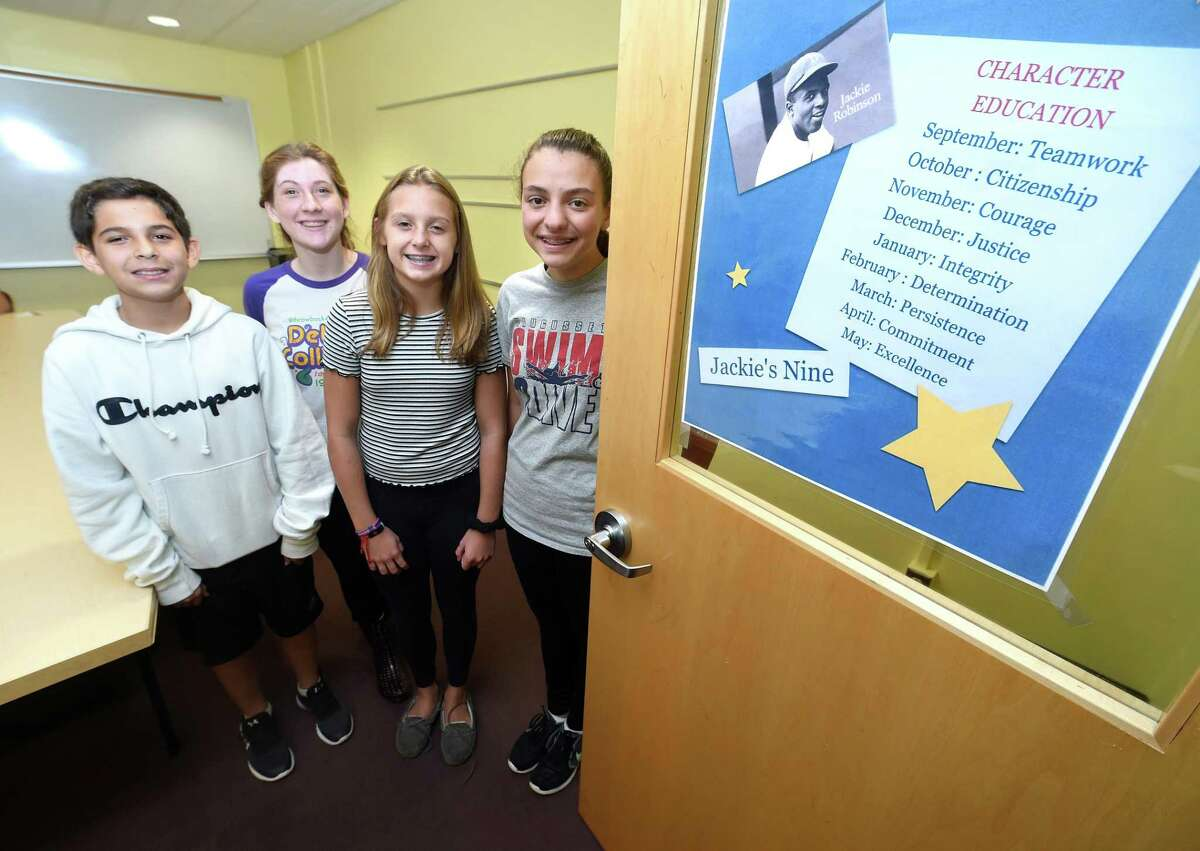 Left to right, Amity Middle School eighth graders Jesse Palermo, Zoe May, Emma Kirck and Cassidy Smith photographed at the school in Orange, were honored for their teamwork at school. The school is using the Jackie Robinson character program and teamwork was the character of the month.
