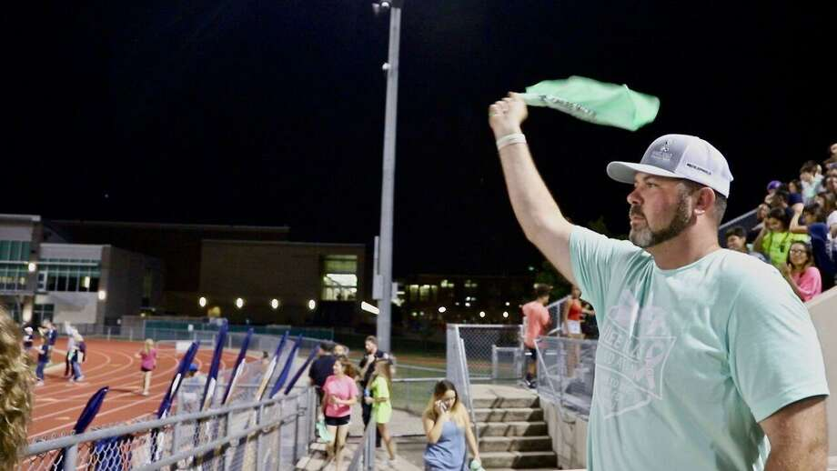 """Davis Mills, father of Kailee Mills, waves a towel during the Klein Collins vs. Klein Oak, Oct. 5, at Klein Memorial Stadium. The Kailee Mills Foundation sponsored the """"Wave to Save Lives"""" event at the football game. Photo: Kailee Mills Foundation"""
