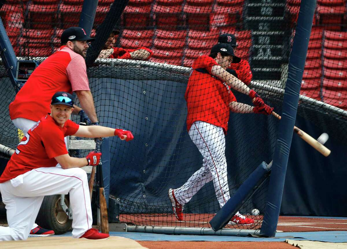 Boston Red Sox's Andrew Benintendi hits in the batting cage as teammates Mitch Moreland, left above, and Brock Holt, below, watch during a workout, Thursday, Oct. 11, 2018, in Boston. The Red Sox face the Houston Astros in Game 1 of baseball's American League Championship Series on Saturday at Boston's Fenway Park. (AP Photo/Elise Amendola)