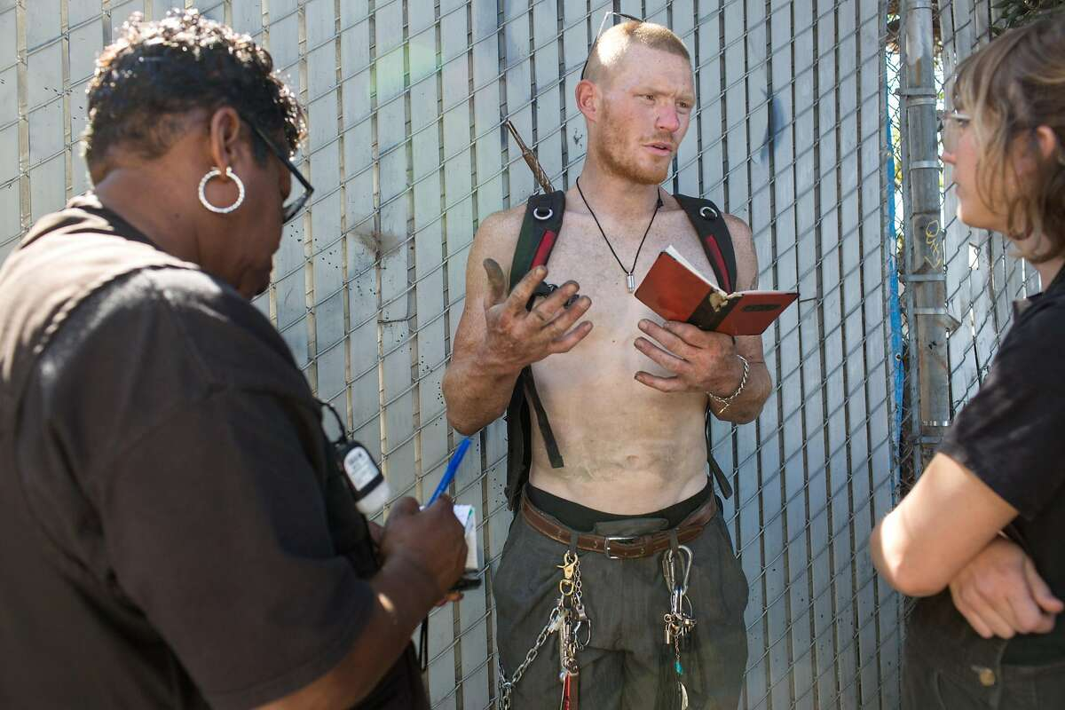 Sage Haithcoat has been on the street for a while. He is a traveler, uninterested in living inside at the moment. He talks to Sharon Thrower (left) and Kiefer Cropper (right), outreach specialists from the Homeless Outreach Team. Bay View on Monday, September 24, 2018 in San Francisco Calif.