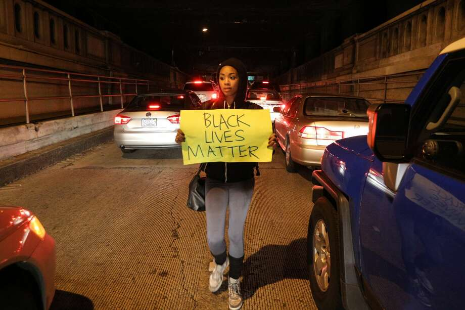 "A protester marches through stopped cars while in the Alameda-Oakland tunnel during a ""Millions March"" demonstration in Oakland protesting the killing of unarmed black men by police in this Dec. 13, 2014 photo. A new study out of UC Berkeley found that less-educated black women who report high levels of racial discrimination may face higher risk of developing chronic diseases. Photo: Elijah Nouvelage/Getty Images"