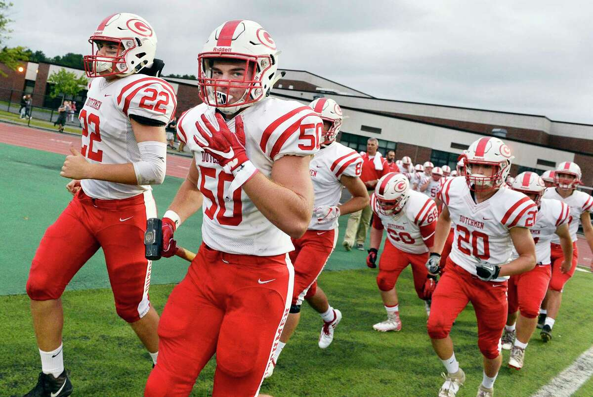 Guilderland lineman #50 Dylan Olson carries a sledge hammer as he leads his team onto the field for their season opener against Shenendehowa Friday August 31, 2018 in Clifton Park, NY. (John Carl D'Annibale/Times Union)