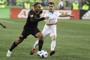 Dynamo forward Arturo Alvarez, left, drives past Seattle Sounders midfielder Victor Rodriguez, right, during the first half of the Dynamo's 4-1 loss Oct. 8 in Seattle.