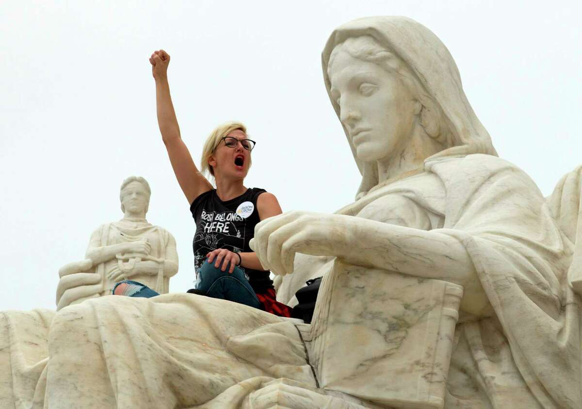 """Demonstrator Jessica Campbell-Swanson of Denver, stands on the lap of the """"Contemplation of Justice"""" statue as protestors take the steps of the US Supreme Court protesting against the appointment of Supreme Court nominee Brett Kavanaugh at Capitol Hill in Washington DC, on October 6, 2018. (Photo by Jose Luis Magana / AFP)JOSE LUIS MAGANA/AFP/Getty Images"""