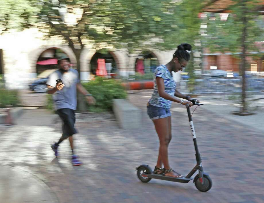 Lex Robinson rides her scooter as DJ Johnson recorders records her at the Pearl.  Photo: Ronald Cortes,  Photo Correspondent / 2018 Ronald Cortes