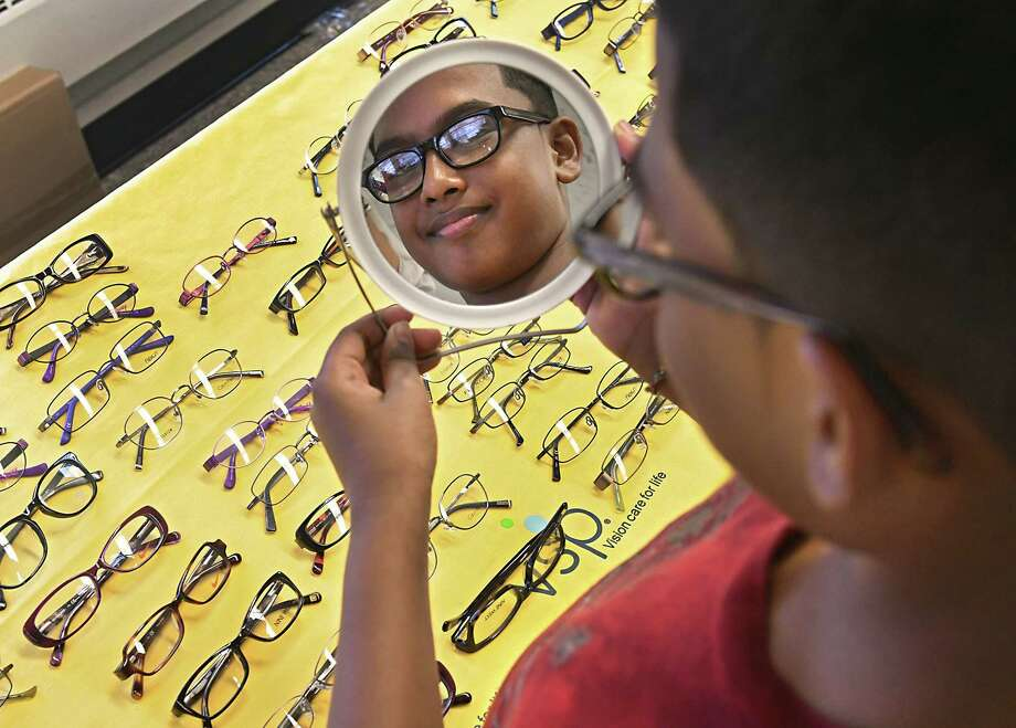 Fifth grader Randy Persaud, 10, picks out a new pair of eyeglasses after receiving a free eye exam at Keane Elementary School on Thursday, Oct. 11, 2018 in Schenectady, N.Y. New York State Education Department, the New York State Optometric Association (NYSOA), VSP Global, and the New York State Society of Opticians (NYSSO offered students to receive comprehensive no-cost vision exams and eyeglasses. (Lori Van Buren/Times Union) Photo: Lori Van Buren / 20045099A
