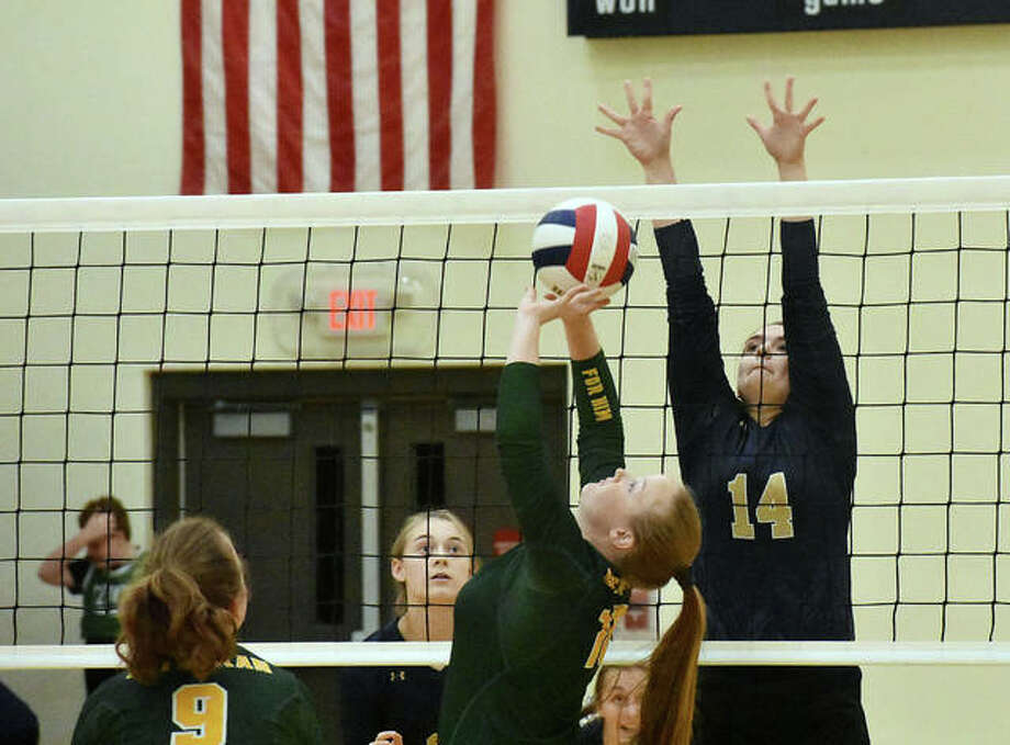MELHS setter Sidney Vetter puts up a pass with FMCHS middle Madison Webb going up for a potential block in the first game. Photo: Matt Kamp/Intelligencer