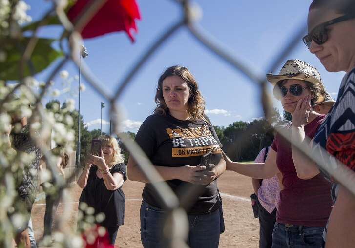 Gail Courchesne, the sister of Emily Courchesne who was shot and killed in October 2017, is comforted while looking at a picture board during a memorial service for Emily Courchesne on the one year anniversary of her death held at Willow Pass Community Park in Concord, Calif. Saturday, Oct. 6, 2018.