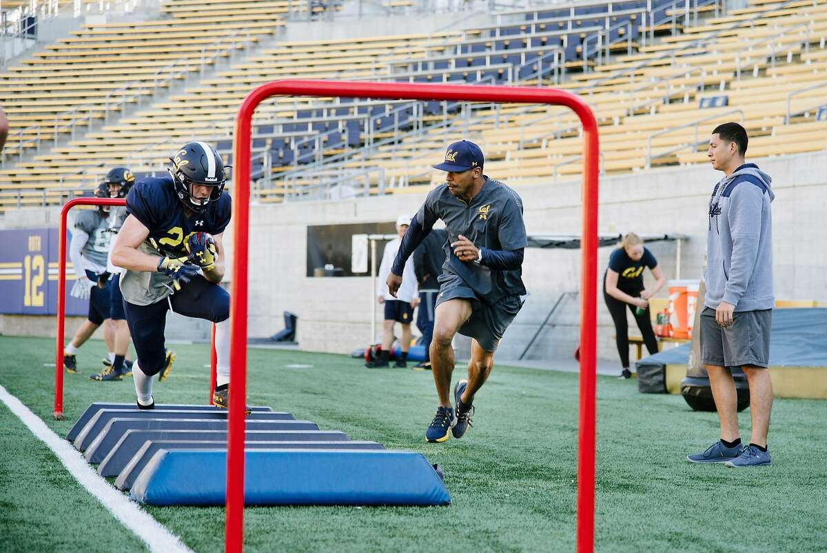 Running back coach Burl Toler III, center, runs along side Patrick Laird during a Cal Bears football practice at Memorial Stadium in Berkeley, Calif., on Tuesday September 25, 2018