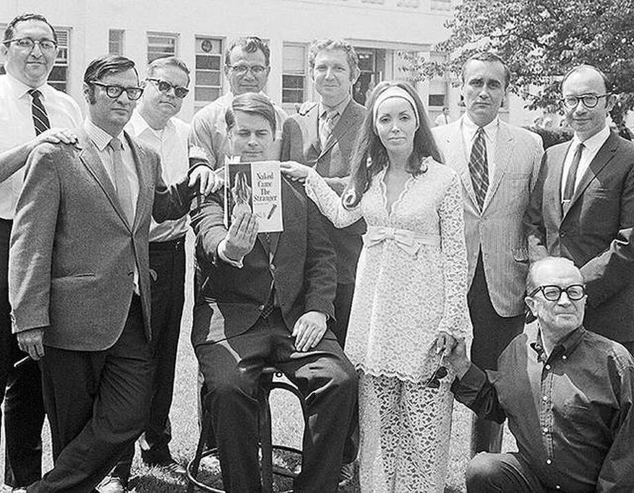 "Nine of the 25 authors of ""Naked Came the Stranger"" get together after they revealed they had perpetrated what may become the literary hoax of the century. The authors, all writers for the newspaper Newsday, wrote the book because they were fed up with what they called the ""trash"" being published as literature. Seated and displaying a copy of the book is columnist Mike McGrady, who conceived the idea, and his sister-in-law, Mrs. Billie Young, who lent herself to the project as the book's ""author,"" Penelope Ashe. Others (standing, left to right) are: Martin Boskin; Harvey Aronson; John Cummins; Tony Insolia; Jack Schwartz; Bob Wiemer; Stan Green; and Val Duncan."