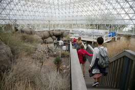 In this Friday, July 31, 2015, photo, tourists walk through the enclosed coastal fog desert ecosystem of the Biosphere 2 in Oracle, Ariz. Biosphere 2 lives on as a successful research site 25 years after eight people emerged from the New Age-style experiment in the Arizona desert. (AP Photo/Ross D. Franklin)