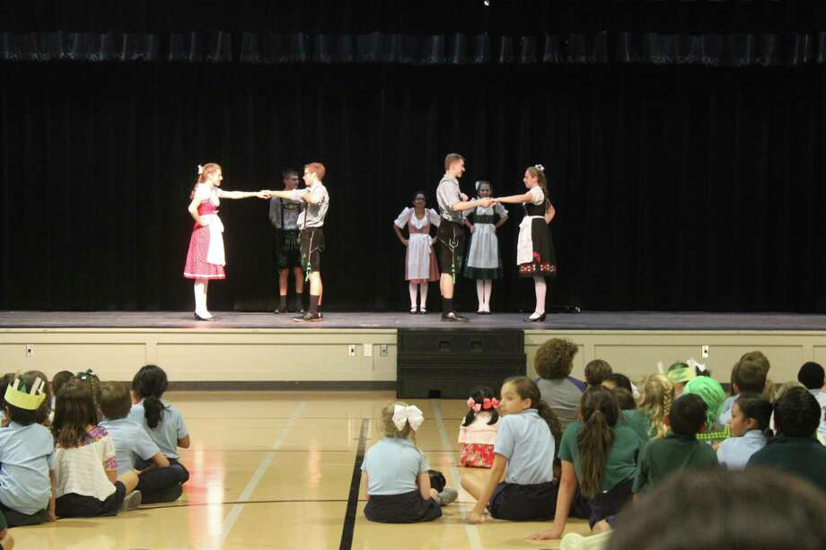 Members of The Woodlands High School's German Dance Troupe take the stage at St. Anthony of Padua Catholic School's International Day Oct. 5 to demonstrate their dances while wearing traditional dress. Photo: Jane Stueckemann/The Villager / Jane Stueckemann/The Villager