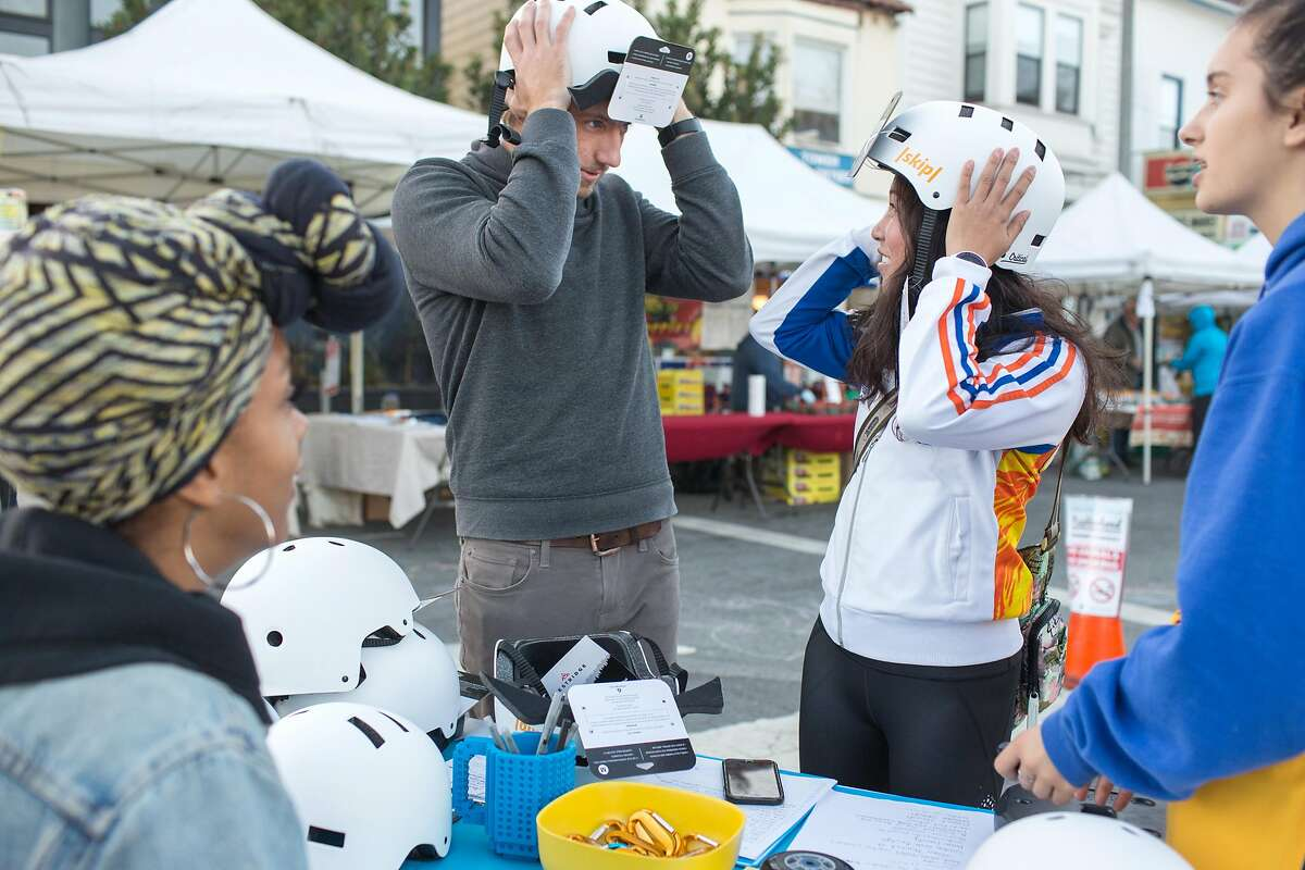 Taylour Miller-Fisher, (left), Skip outreach team representative, with a helper Aki Nitta-Mack (right), talk to Erik McGregor and Qiu Xie who are trying on helmets at the demonstration booth of Skip, a scooter rental company, at the Castro Farmers' Market. Wednesday, October 10, 2018 in San Francisco, Calif.