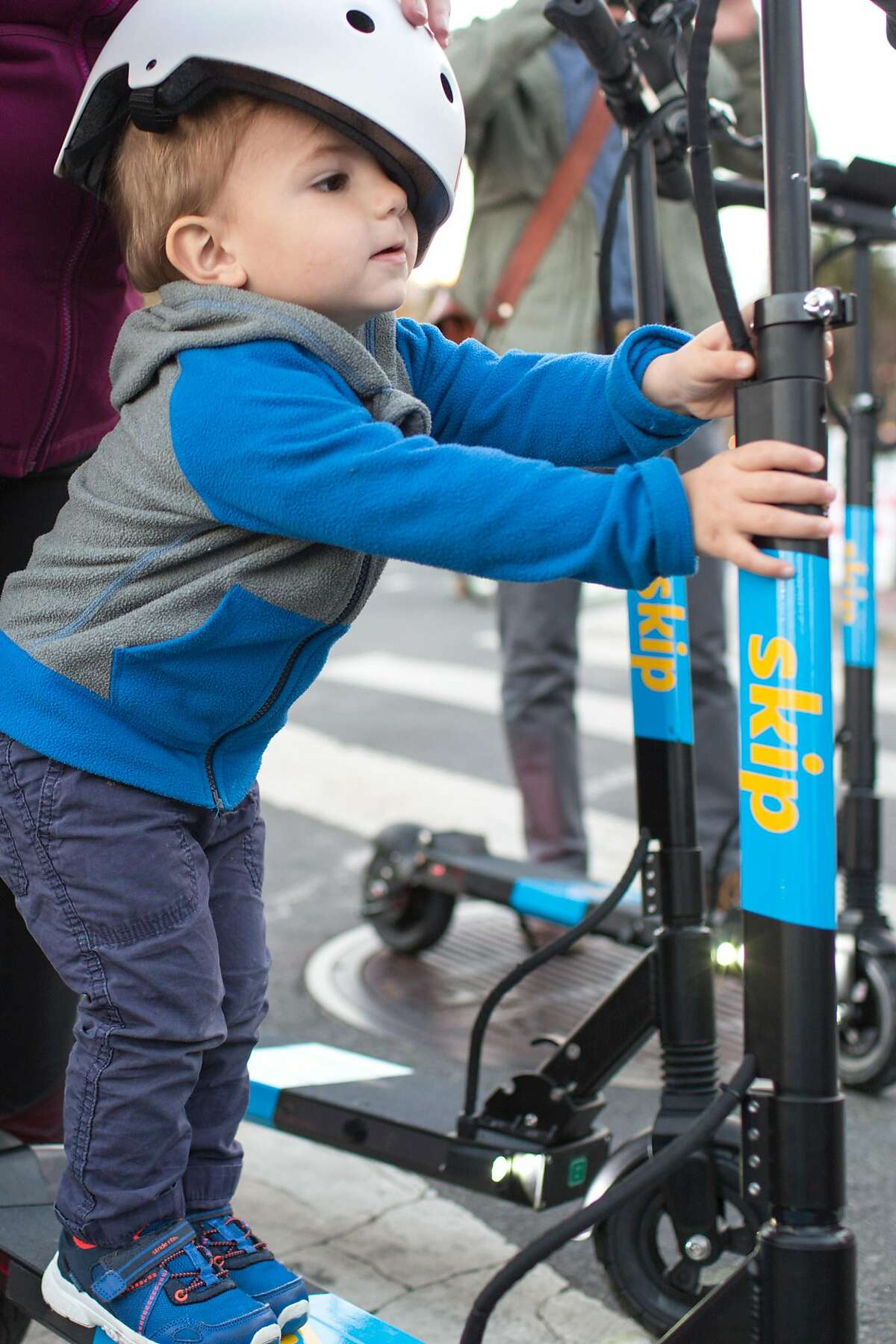Milo, 23 months, stands on a Skip scooter held by his mom Susan Kimberlin at the demonstration booth of Skip, a scooter rental company, at the Castro Farmers' Market. Wednesday, October 10, 2018 in San Francisco, Calif.