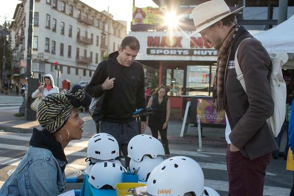 Taylour Miller-Fisher, Skip outreach team representative, talks to Leigh Christie (right) and Allen Saakyan at the demonstration booth of Skip, a scooter rental company, at the Castro Farmers' Market. Wednesday, October 10, 2018 in San Francisco, Calif.