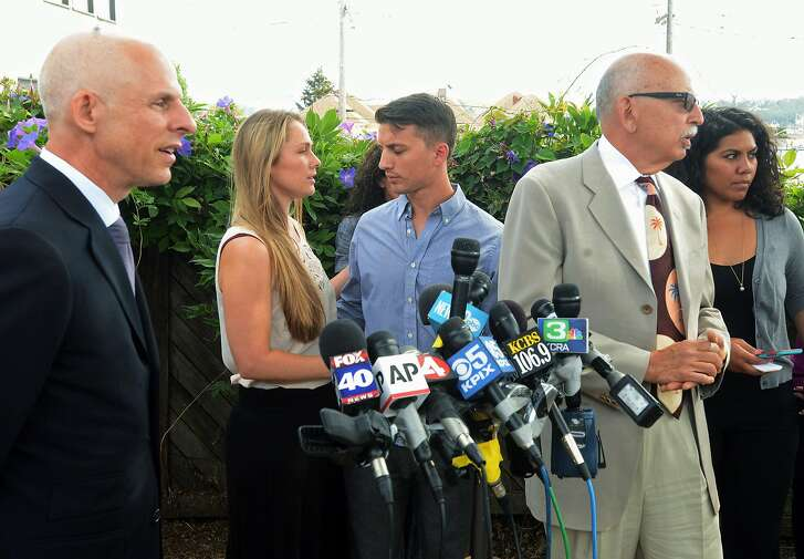 Denise Huskins and her boyfriend, Aaron Quinn, turn to each other at the end of a news conference on Monday, July 13, 2015, in Vallejo, Calif. At left is Huskins' attorney, Douglas Rappaport and second from right is Quinn's attorney, Daniel Russo. The lawyers for a couple in a kidnap-for-ransom case that police called a hoax are blasting investigators and asking that authorities set the record straight. Russo said Vallejo Police detectives rushed to judgment and that he and Rappaport want the public perception of their clients changed. Quinn and a teary-eyed Denise Huskins held hands and hugged at the end of the news conference, but did not talk to reporters. (Mike Jory/Vallejo Times-Herald via AP)
