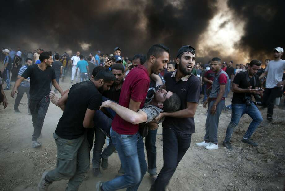 Palestinian protesters evacuate a man shot by Israeli troops at the Gaza Strip border. The Israeli military said 14,000 Palestinians thronged the fence areas. Photo: Khalil Hamra / Associated Press