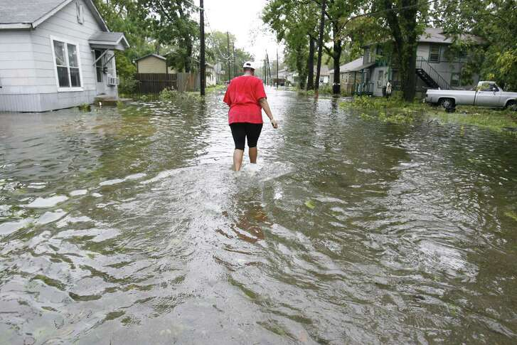 A resident walks a flooded street in the Independence Heights neighborhood north of 610, where flooding after heavy rains is common.