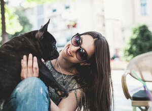 Beautiful teenage girl sitting in cafe restaurant with her adorable French bulldog puppy. People and dogs theme.