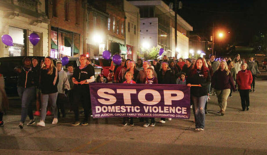Marchers walk Thursday evening along State Street near the intersection of W. Third Street during the Fifth Annual Alton Police Department Walk Against Domestic Violence. About 125 marchers came out for the walk from SS Peter and Paul Catholic Church to the Liberty Bank Amphitheater. Photo: Scott Cousins | The Telegraph