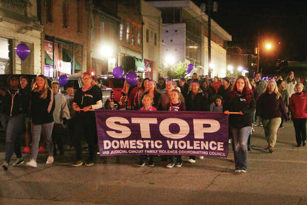 Marchers walk Thursday evening along State Street near the intersection of W. Third Street during the Fifth Annual Alton Police Department Walk Against Domestic Violence. About 125 marchers came out for the walk from SS Peter and Paul Catholic Church to the Liberty Bank Amphitheater.