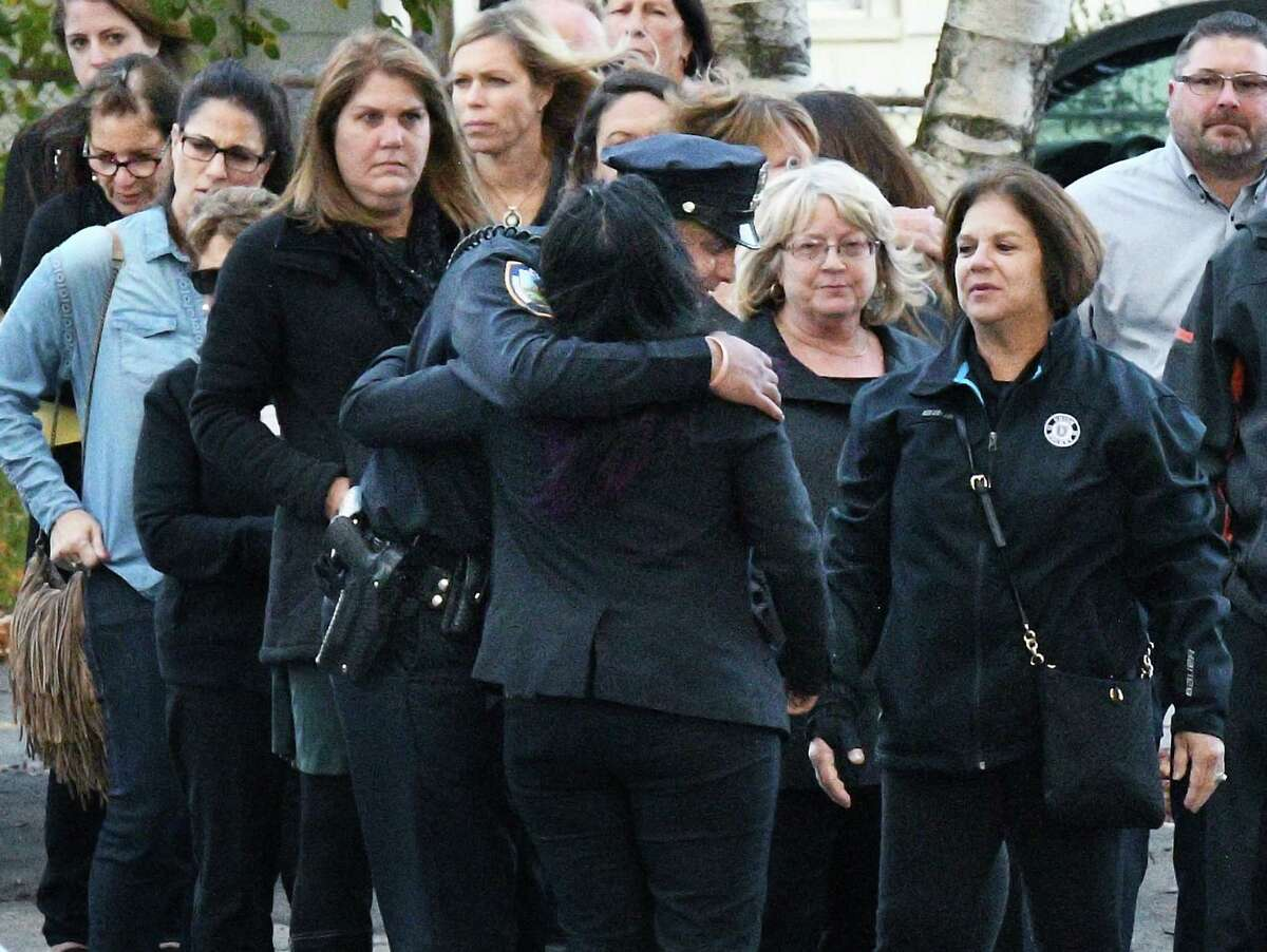 """A policeman hugs a mourner in line for the combined services for Schoharie limo crash victims for Abigail (King) Jackson, Adam """"Action"""" Jackson, Mary (King) Dyson, Robert J. Dyson, Allison A. King, Amy (King) Steenburg, Axel J. Steenburg and Richard Steenburg Jr., St. Stanislaus Roman Catholic Church Friday Oct. 12, 2018 in Amsterdam, NY.(John Carl D'Annibale/Times Union)"""