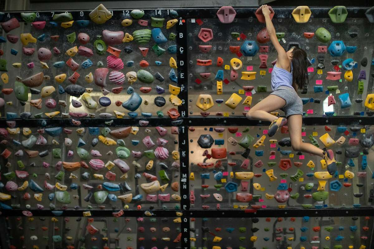 Abbie Cheng, 13, climbs a wall at Planet Granite on Thursday, Sept. 27, 2018, in San Francisco, CA. San Francisco advances to California's least-restrictive tier for reopening, expanding access to indoor climbing gyms, movie theaters, houses of worship and more.