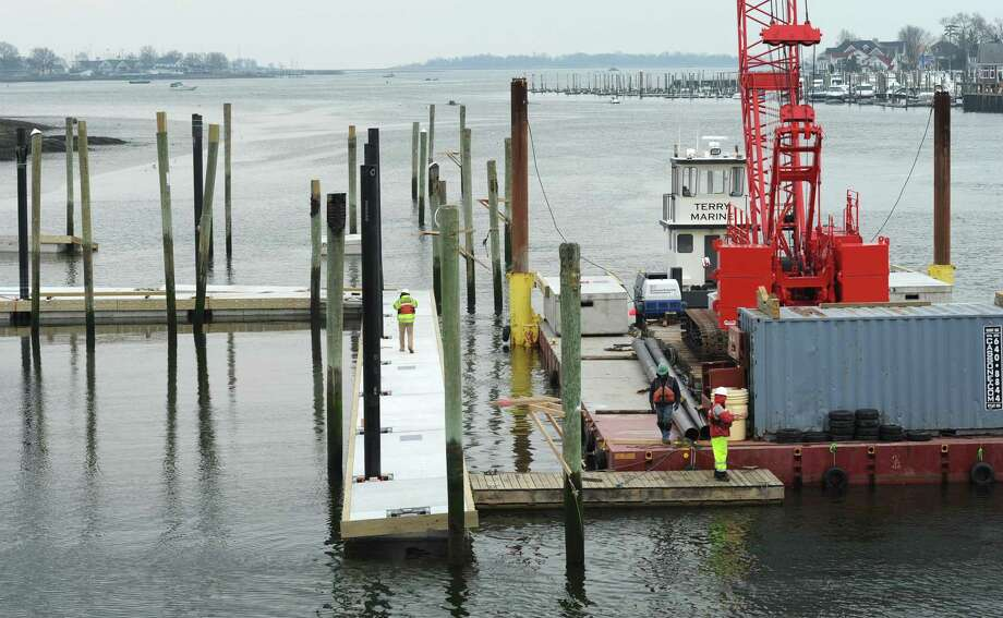 Workers with Terry Marine install the 8-ton dock sections at Veterans Memorial Park in April. Photo: Erik Trautmann / Hearst Connecticut Media / Norwalk Hour