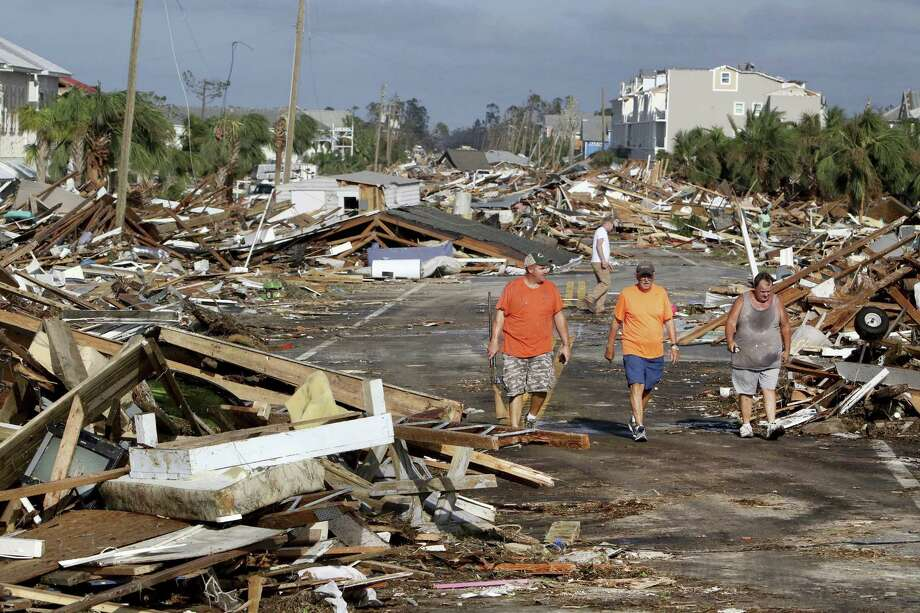 From left: Lee Cathey, 37, Al Cathey, 71, and Charles Smith, 56, survey damage in the coastal township of Mexico Beach, Fla., population 1,200, which lay devastated on Thursday after Hurricane Michael made landfall on Wednesday in the Florida Panhandle. Climate change left unchecked mean more such disaster ahead. Photo: Douglas R. Clifford /Associated Press / Tampa Bay Times