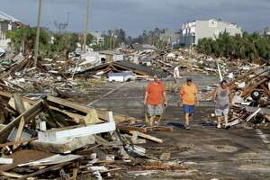 From left: Lee Cathey, 37, Al Cathey, 71, and Charles Smith, 56, survey damage in the coastal township of Mexico Beach, Fla., population 1,200, which lay devastated on Thursday after Hurricane Michael made landfall on Wednesday in the Florida Panhandle. Climate change left unchecked mean more such disaster ahead.