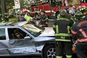 Paramedics and fire crews treat one person who was injured in a three vehicle crash at the intersections of Lafayette Boulevard and State Street in Bridgeport, Conn., on Friday Oct. 12, 2018.