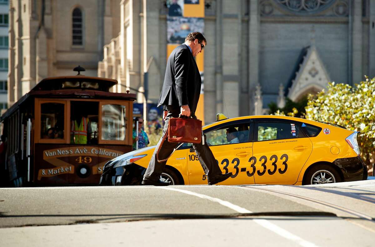 A taxi crosses California St. on Friday, Oct. 12, 2018, in San Francisco.