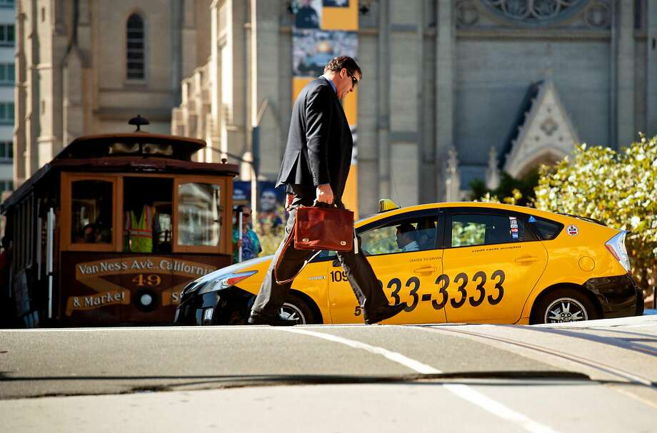 A taxi crosses California Street in San Francisco where cabdrivers have lost many of their monthly trips to the fiercely competitive ride-hailing firms. Photo: Noah Berger / Special To The Chronicle