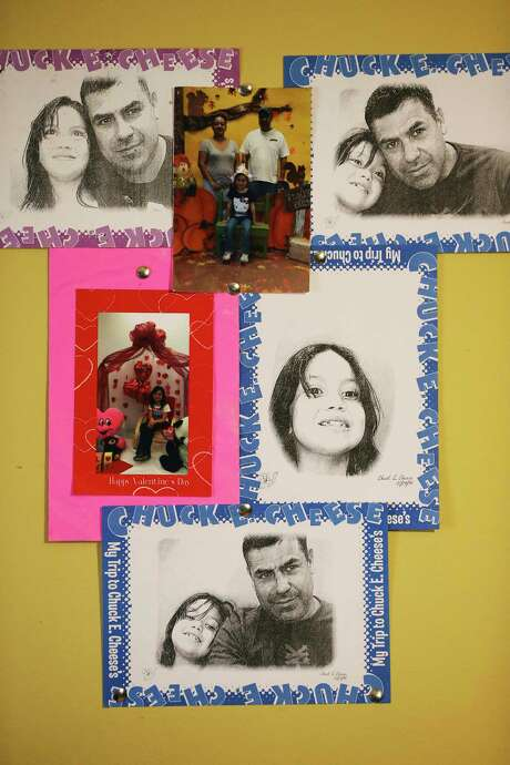 Family photos decorate a wall in Sandro Alejandro Garcia Moreno's room in the Rio Grande Valley, Thursday, Sept. 27, 2018. He recently moved into the room at a house with two other Mexican immigrants. He works day jobs to pay rent and support his wife and 11-year-old daughter in Mexico. Photo: JERRY LARA, San Antonio Express-News / © 2018 San Antonio Express-News
