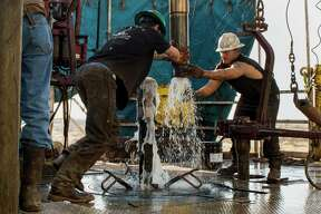Workers connect drill bits and drill collars, used to extract natural petroleum, at an Endeavor Energy Resources drilling site in the Permian Basin.