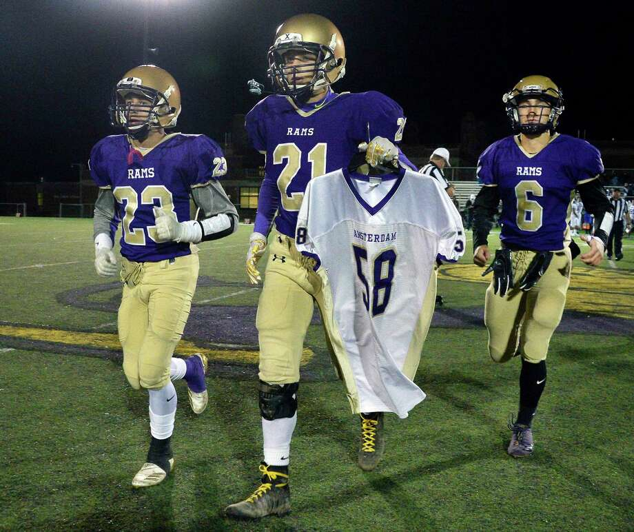 "Amsterdam High team captains, from left, Peyton Ausfeld, Trey Ausfeld and Andrew Giaimo carry the jersey of alum Adam ""Action"" Jackson, a victim of the Schoharie limo crash at the start of their game against La Salle Friday Oct. 12, 2018 in Amsterdam, NY.  (John Carl D'Annibale/Times Union) Photo: John Carl D'Annibale, Albany Times Union / 20045098A"