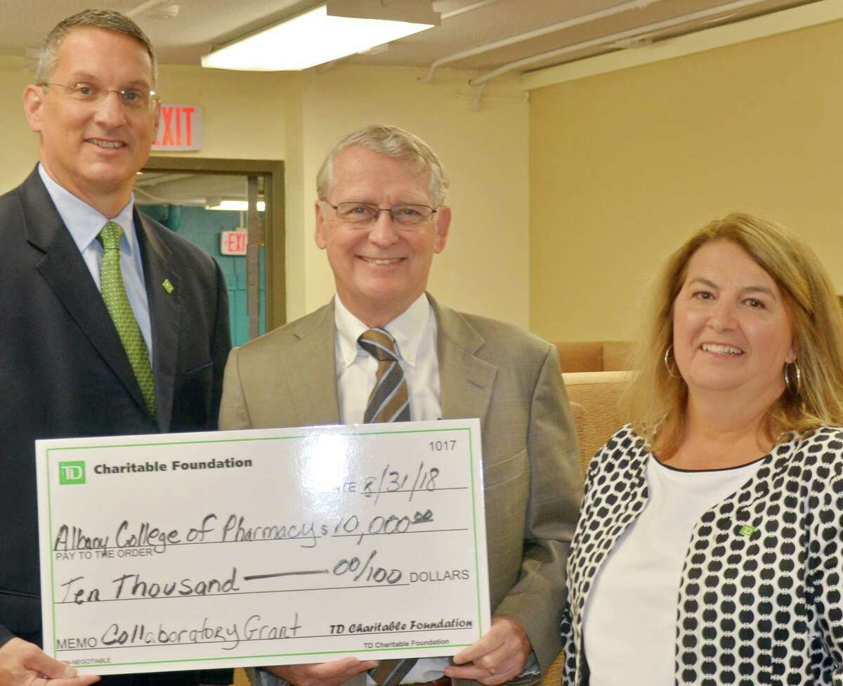 James Gaspo, Upstate NY Regional Vice President at TD Bank (left) and Francine Yanulavich, TD Bank?s Vice President and Field Marketing Manager (right), present Albany College of Pharmacy and Health Sciences President Greg Dewey with a $10,000 check on behalf of the TD Charitable Foundation. The funds will help ensure The Collaboratory ? a new community health resource opened by the College and located in Albany?s South End ? has the resources needed to provide a range of social and health care services for area residents.