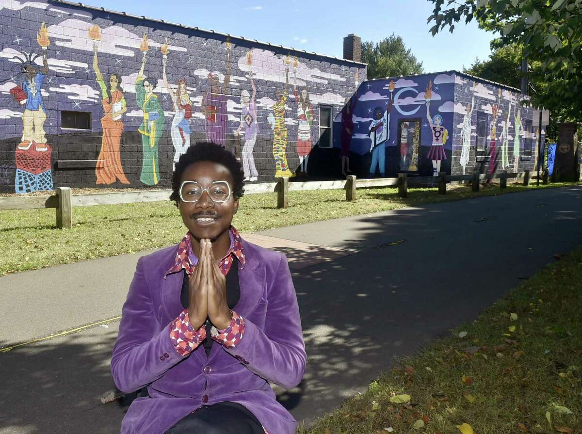 Artist Kwadwo Adae is photographed in front of a mural he of Bethany and the Adae Fine Arts Academy in New Haven with his Women's Empowerment Mural on the Farmington Canal Greenway Friday on Goodrich Street near Dixwell Ave. Adae received approximately $26,000 in grants for the project.