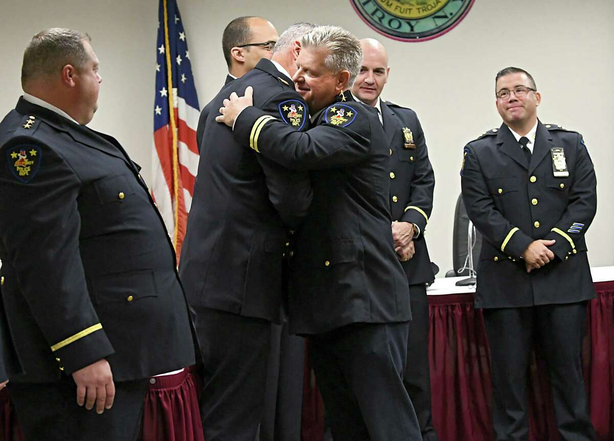 Daniel DeWolf, right, gets a hug from Captain Matthew Montanino after being promoted from Troy Assistant Chief of Police to Deputy Chief at Troy City Hall on Friday, Oct. 12, 2018 in Troy, N.Y. (Lori Van Buren/Times Union)