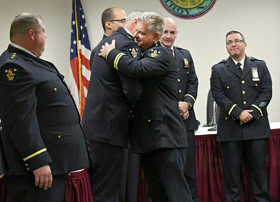 Daniel DeWolf, right, gets a hug from Captain Matthew Montanino after being promoted from Troy Assistant Chief of Police to Deputy Chief at Troy City Hall on Friday, Oct. 12, 2018 in Troy, N.Y.  (Lori Van Buren/Times Union) Photo: Lori Van Buren / 20045097A